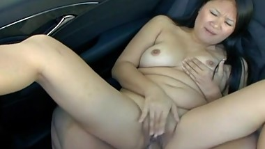 Busty brunette Asian being naughty in the car